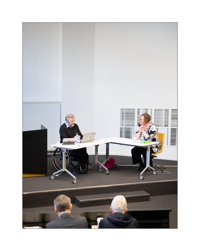 Per-Olof Hedvall och Helena Taubner sitter på podiet i en föreläsningssal